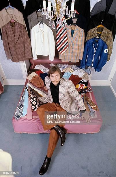 Men's Fashion France Paris 1973 JeanClaude BOUTTIER boxeur français pose assis sur un lit recouvert de cravates chamarées et de chemises vêtu d'une...