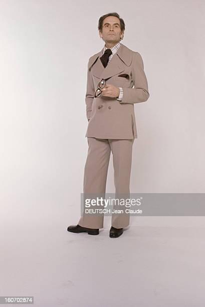 Men's Fashion France Paris 1973 Les ténors de la haute couture Pierre CARDIN pose debout une paire de lunettes dans sa main gauche en costume deux...