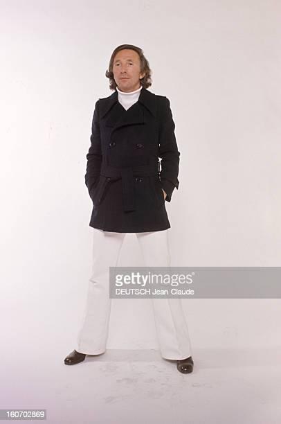 Men's Fashion France Paris 1973 Les ténors de la haute couture Ted LAPIDUS cheveux milongs pose debout jambes écartées et porte un col roulé blanc...