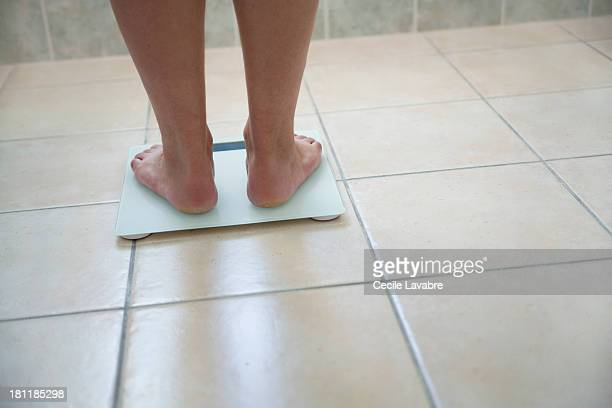 Men's feet on a weighing scale