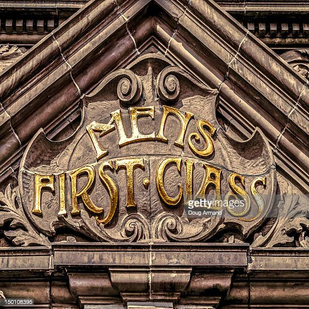 'Mens First Class' sign on an old building facade