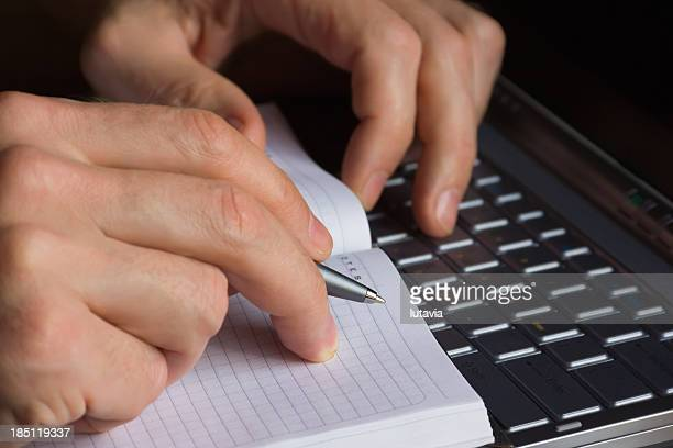 men's hands writing a pen in notebook from computer information - lutavia stock pictures, royalty-free photos & images