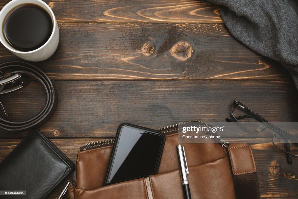 Men's Satchel Bags, Mobile Phone and Male Personal Belongings on Rustic Wood : Stock Photo