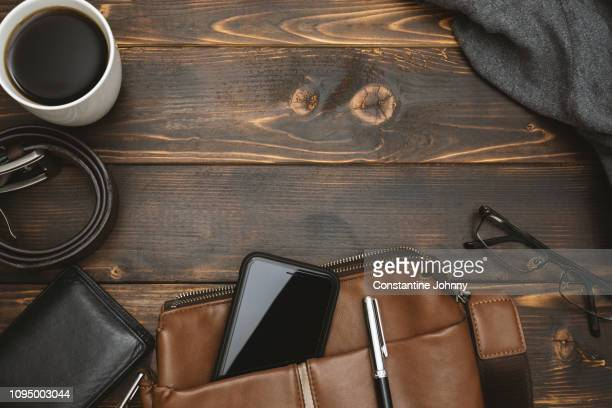 men's satchel bags, mobile phone and male personal belongings on rustic wood - mannelijke gelijkenis stockfoto's en -beelden