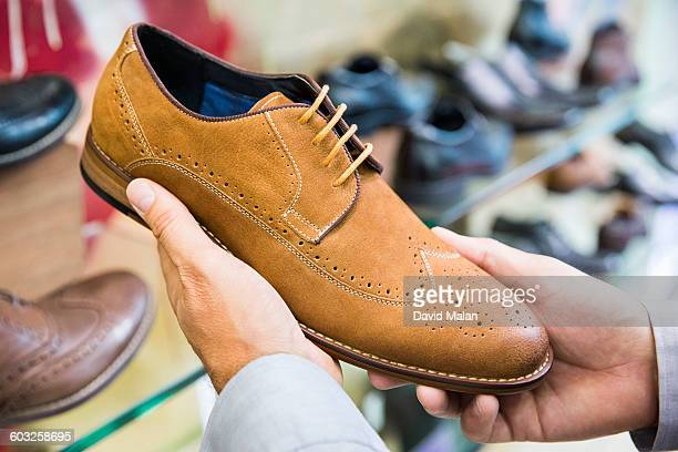A mens shoe being looked at in a shoe store.