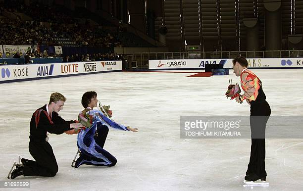Men's singles gold medalist Johnny Weir of US and silver medalist Timothy Goebel of US cheer bronze medalist Frederic Dambier of France after the...