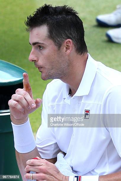 Mens Singles SemiFinal Kevin Anderson v John Isner John Isner blows on a finger injury at All England Lawn Tennis and Croquet Club on July 13 2018 in...
