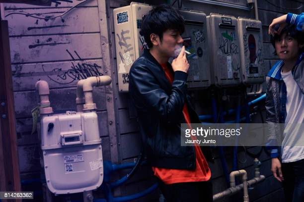 mens street style portrait in shinjuku - タバコを吸う ストックフォトと画像