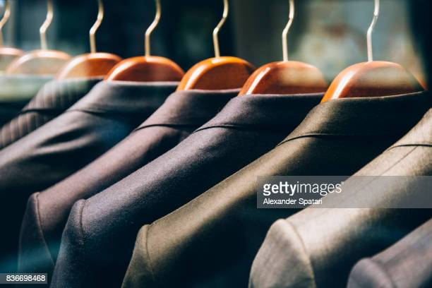 Men's suits hanging in a row on clothing rack
