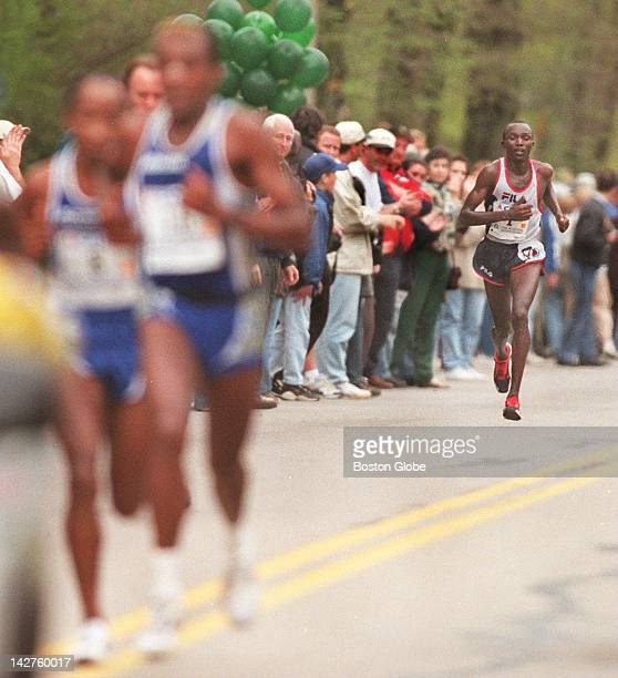 Men's winner Moses Tanui of Kenya right begins to make his move on the leader pack in Newton during the later part of the 1998 Boston Marathon Monday