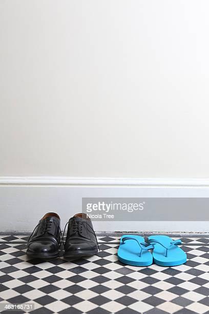 Mens work shoes next to flip flops in hallway