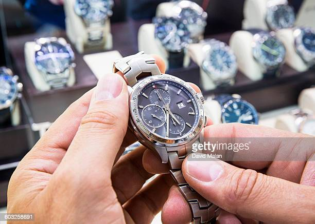 Mens wristwatch being held in a watch shop.