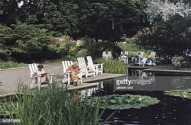 Menschen entspannen sich auf weißen Holzstühlen an einem künstlich angelegten Teich mit Seerosen in Planten un Blomen Aufgenommen um 1991