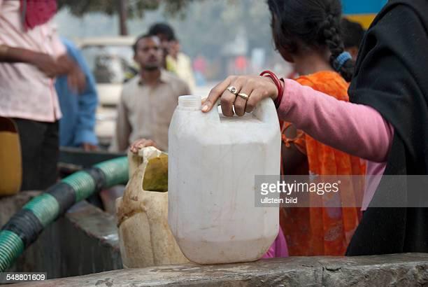 Menschen holen Wasser von einem öffentlichen Wagen