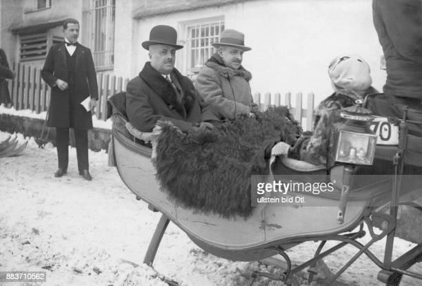Menschen im Schlitten in einer verschneiten Siedlung Originalaufnahme im Archiv von ullstein bild