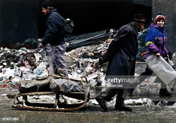 Menschen in Sarajewo suchen im Müll der an der Strasse liegt nach Verwertbarem ein alter Mann zieht einen Schlitten mit Brennholz November 1993