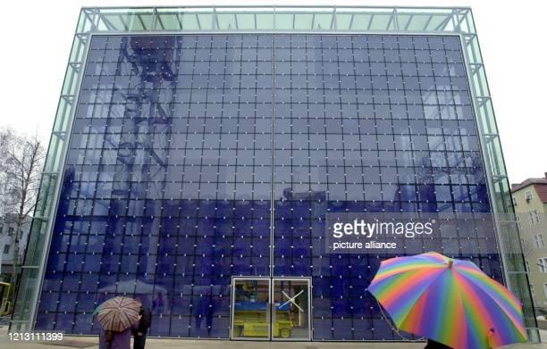 Menschen mit Regenschirmen stehen am vor der HerzJesuKirche in München mit dem größten Kirchenportal der Welt Das von dem ukrainischen Künstler...