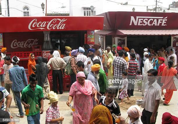Menschen trinken Limonade vor Staenden von Coca Cola und Nescafe
