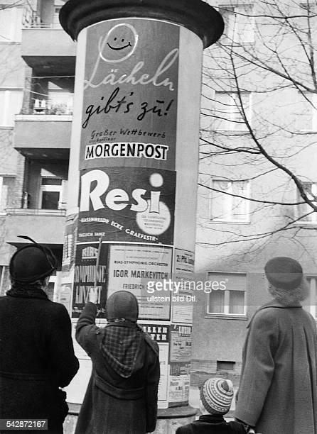 Menschen vor einer Litfaßsäule in Berlin darauf Reklame für die Berliner Morgenpost das Tanzlokal Resi und Konzerte des RiasSinfonieorchesters1950er...