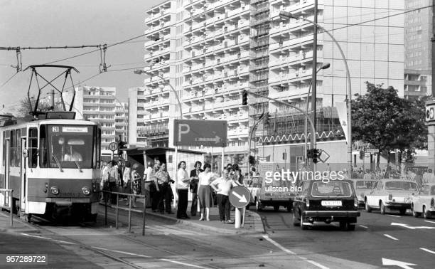 Menschen warten nach Feierabend an einer StraßenbahnHaltestelle in der Greifswalder Strasse im Stadtbezirk Prenzlauer Berg in Berlin Aufgenommen im...