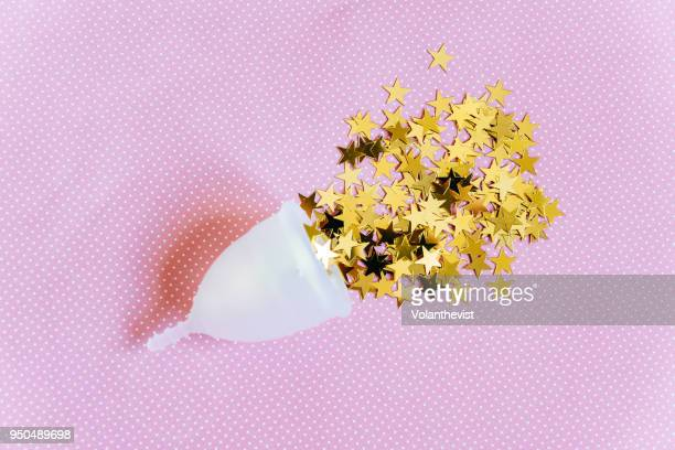Menstrual cup with bright stars on pink background