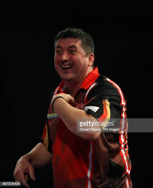 Mensur Suljovic celebrates winning his match during day nine of the William Hill World Darts Championship at Alexandra Palace London