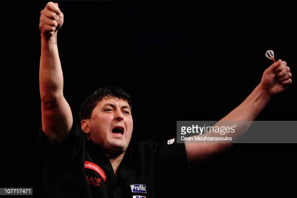 Mensur Suljovic of Austria celebrates his win against Michael van Gerwen of Holland during day 6 in the 2011 Ladbrokescom World Darts Championship at...
