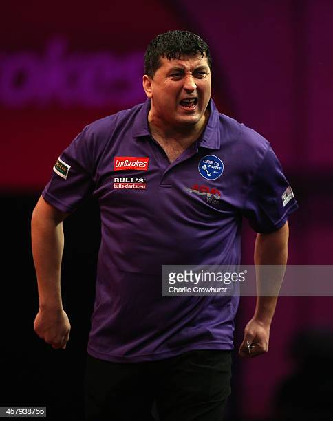 Mensur Suljovic of Austria celebrates winning a leg during his first round match against Mark Webster of Wales during the Ladbrokescom World Darts...