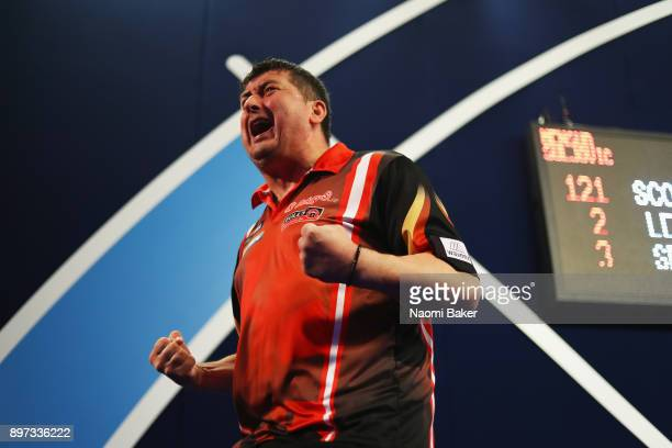 Mensur Suljovic of Austria celebrates winning the second round match against Robert Thornton of Scotland on day nine of the 2018 William Hill PDC...