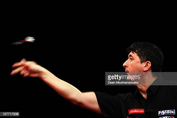 Mensur Suljovic of Austria in action against Michael van Gerwen of Holland during day 6 in the 2011 Ladbrokescom World Darts Championship at...