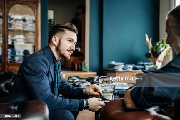 menswear store clerk helping customer with fabric swatches - herrenkleidung stock-fotos und bilder