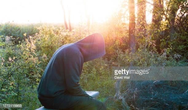 a mental health concept of a moody, hooded figure, sitting on a bench. back lighted by the evening sun. - rural scene stock pictures, royalty-free photos & images