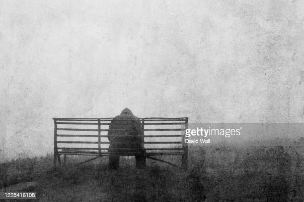 a mental health concept of mysterious figure back to camera,  sitting on a bench alone. with a grunge, textured edit. - suicidio foto e immagini stock