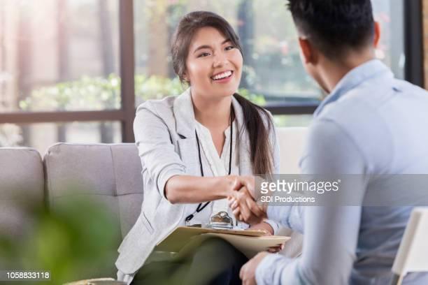paciente e o profissional de saúde mental, calorosamente, apertar as mãos antes da reunião - clínica médica - fotografias e filmes do acervo