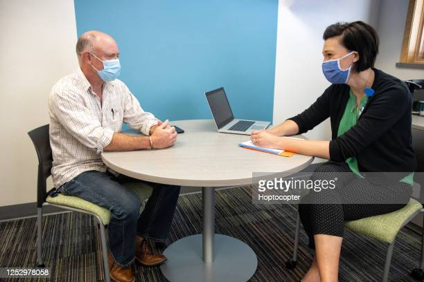 a mental health professional in her forties wearing a face mask talks with a masked white male in his sixties while sitting at a table in a medical clinic - interview stock pictures, royalty-free photos & images