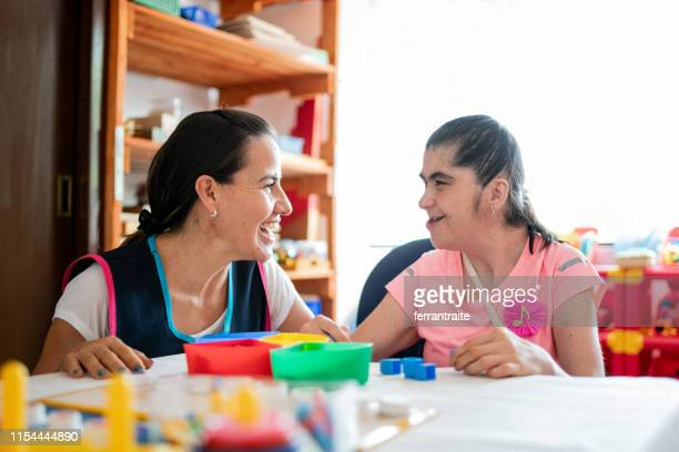 mental health professional playing with down syndrome woman - learning disability stock pictures, royalty-free photos & images