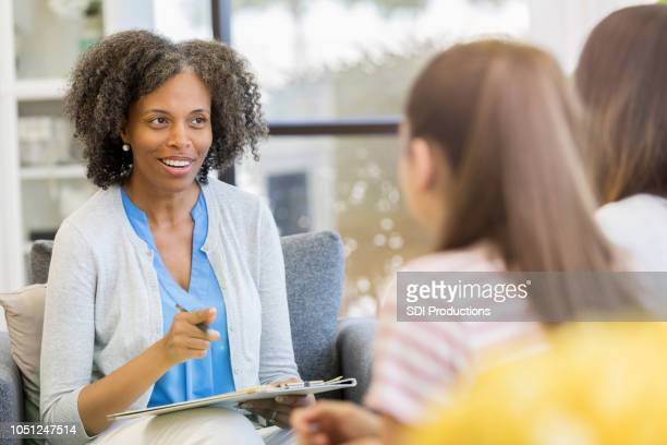 mental health professional speaks candidly with two patients - mental health professional stock pictures, royalty-free photos & images