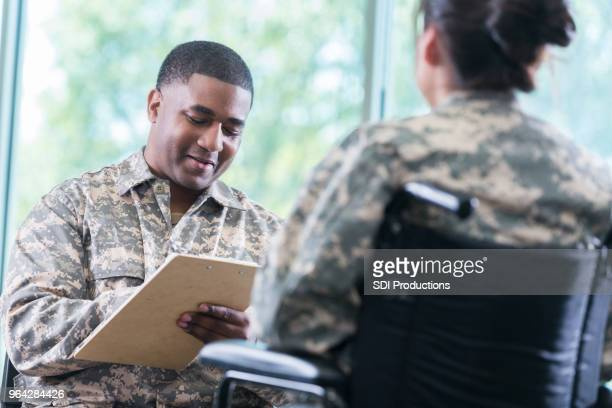 mental health professional talks with injured soldier - military doctor stock photos and pictures