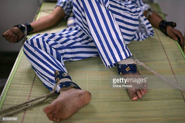 A mental patient who suffers from schizophrenia caused by the Sichuan earthquake lies in bed with arms and legs being bound at the Anxian Mental...