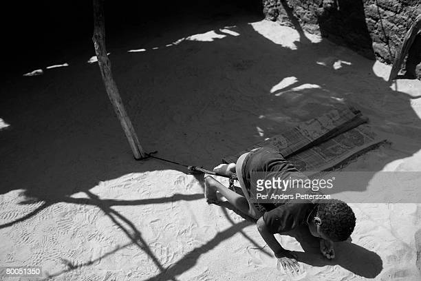 Mentally handicapped boy is tethered to a pole to prevent him from wandering away at the Oure Cassoni refugee camp on July 26, 2007 about 23...