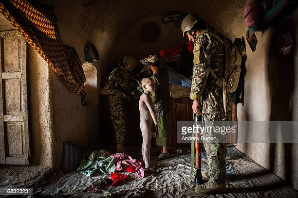 A mentally handicapped boy stares at a soldier in the Afghan National Army's 6th Kandak 3rd company during a routine housesearch on a joint patrol...