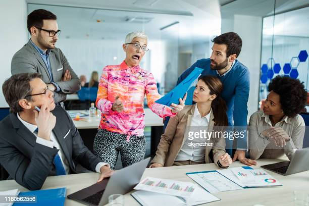 mentally ill businesswoman reading shocking reports on a meeting with her colleagues. - insanity stock pictures, royalty-free photos & images
