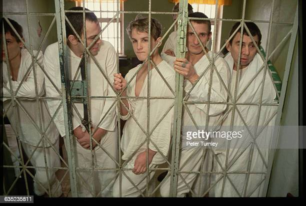 Mentallyill patients stand behind the cell bars of their hospital room at a psychiatric ward | Location near Moscow Russia