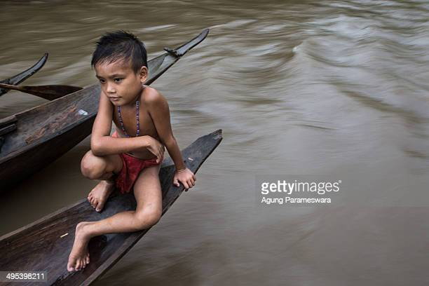 Mentawanese boy sits on a traditional canoe as he play with her brother on May 26 2014 in Butui Village Siberut Island West Sumatra Indonesia Sikerei...