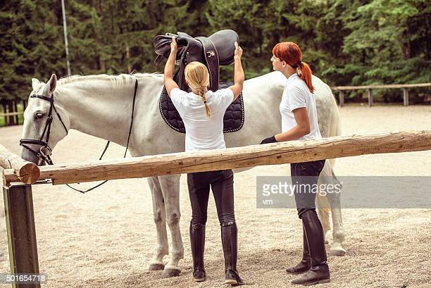 Mentor putting saddle on the horse for her student