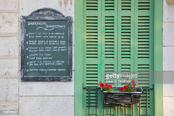 menu board and green shutters of the so caprichos restaurant. - balearic islands stock pictures, royalty-free photos & images