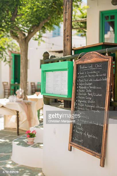 A menu card and restaurant tabels in the town of Ano Meria on June 13 2015 in Folegandros Greece Folegandros is a small island with three villages in...