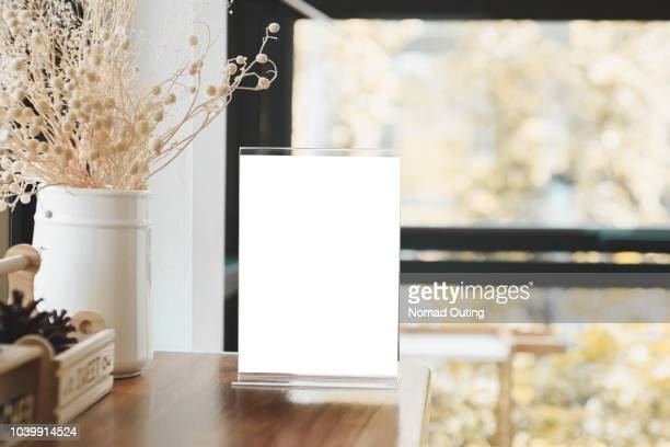 menu card holder with white sheet of paper on table in cafe.card display promotion and information for customer,picture stand,sign holder and photo frame template. - menu stock pictures, royalty-free photos & images
