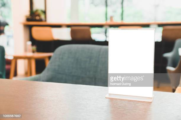 menu card holder with white sheet of paper on table in cafe.card display promotion and information for customer,picture stand,sign holder and photo frame template. - kunstdruck stock-fotos und bilder