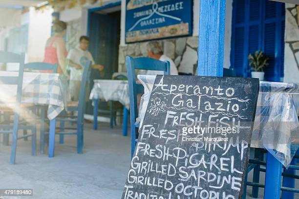 A menu card in front of a open restaurant offers fresh fish on June 19 2015 in Sifnos Greece Sifnos is a island in the western Aegean Sea the surface...